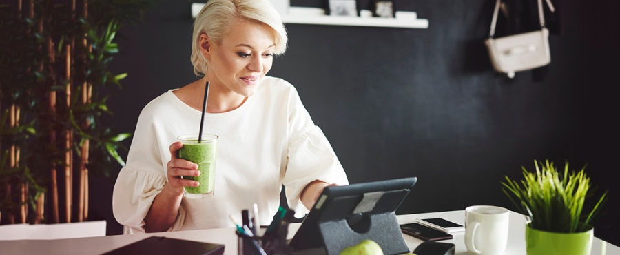 Woman with smoothie using a digital tablet at her desk