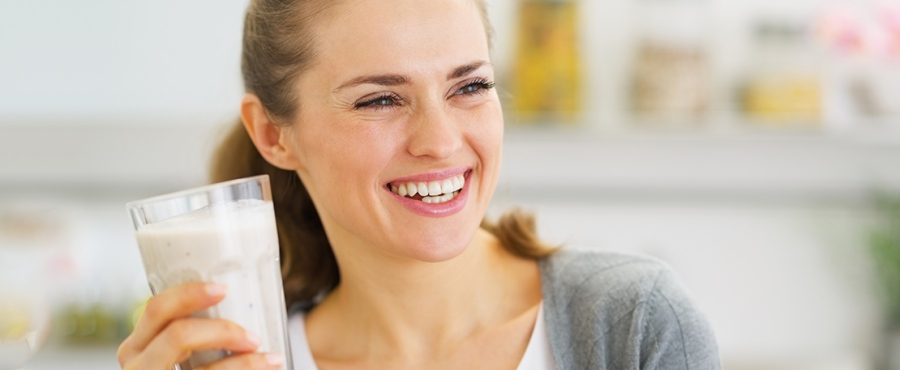 smiling young woman drinking fresh cocktail